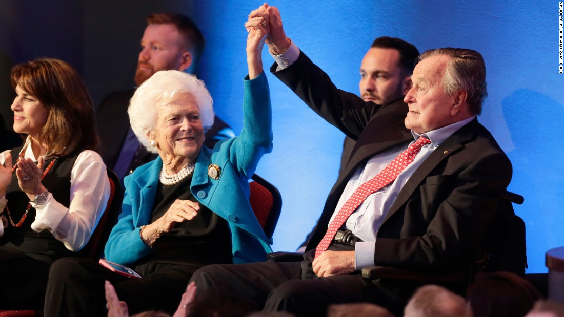 Bush holds up his wife's hand at the Republican presidential primary candidate debate in February 2016. Their son, former Florida Governor Jeb Bush, ran an unsuccessful bid for the nomination.