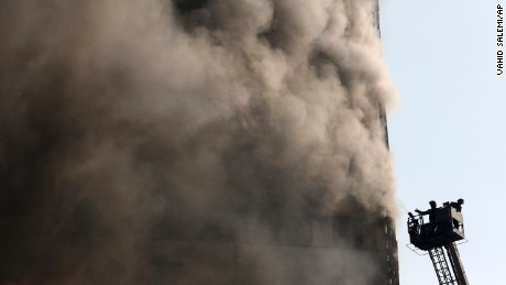 Iranian firefighters work to extinguish the fire at the Plasco building in central Tehran on Thursday.