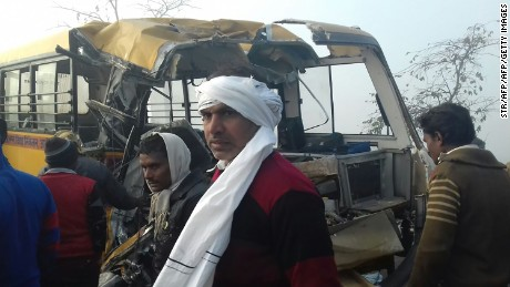 Bystanders gather near the scene of a bus crash in Etah in the state of Uttar Pradesh on January 19, 2017.