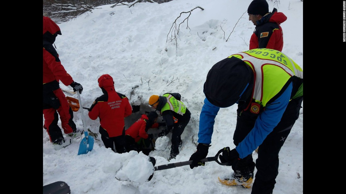 Rescuers dig for avalanche survivors after skiing several kilometers through blizzard conditions to reach the hotel, on January 19.