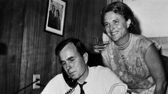 Bush with her husband as he campaigns for the US Senate in 1964. On the desk is a needlepoint bag she made.