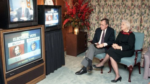 Bush sits with her husband as they watch the presidential election results in Houston on November 8, 1988. Her husband was elected the 41st President that day, with 53.1% of the popular vote and 426 electoral votes. He defeated Democratic nominee Michael Dukakis.