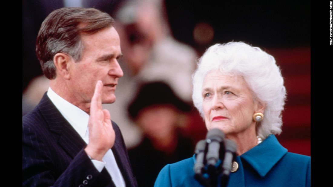 Barbara Bush looks on as her husband takes the oath of office at his inauguration on January 20, 1989.