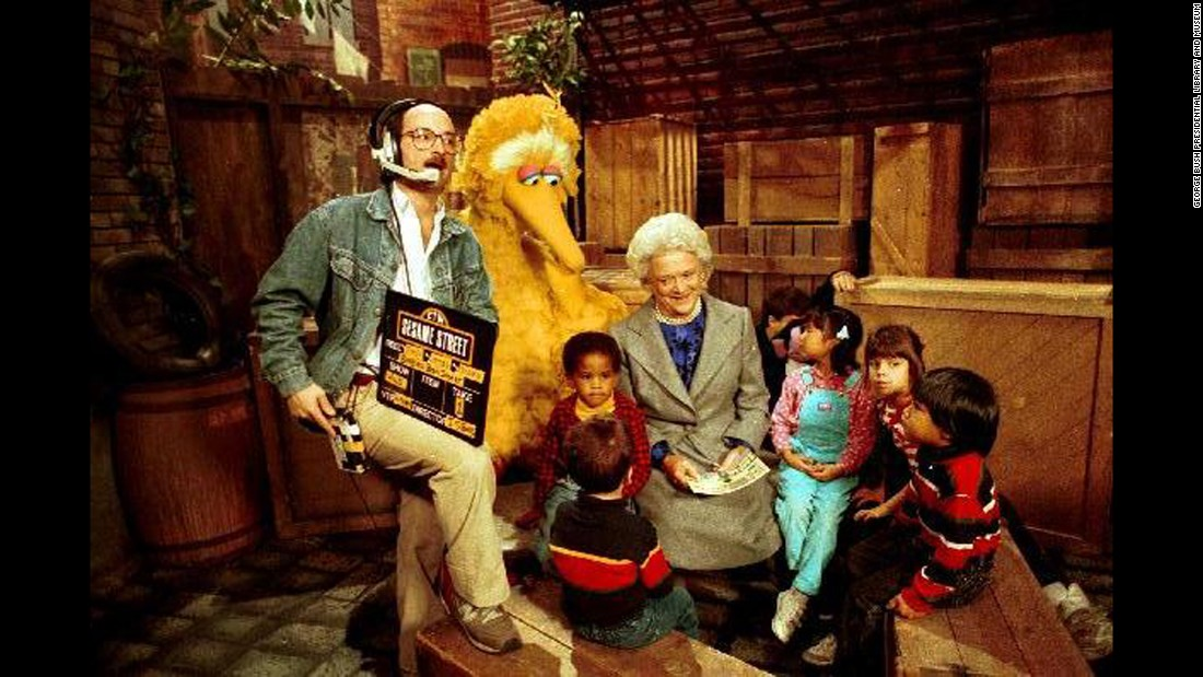 "Bush reads to children and Big Bird on the set of ""Sesame Street"" in October 1989."