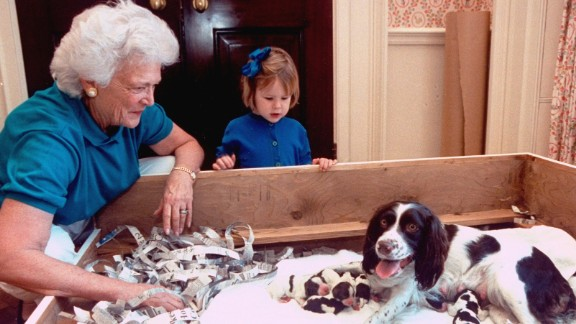 The first lady smiles at new mom Millie after the dog delivered her first litter of six. Bush's granddaughter Marshall looks on.