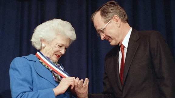 President Bush admires the Harry S. Truman Award for Distinguished Service that his wife received in Washington on March 30, 1989.