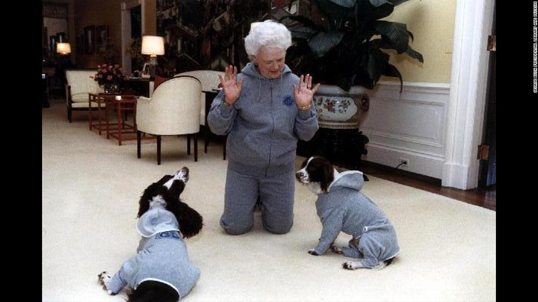 Bush and her dogs, Ranger and Millie, wear matching gray sweatsuits at the White House on January 9, 1991.