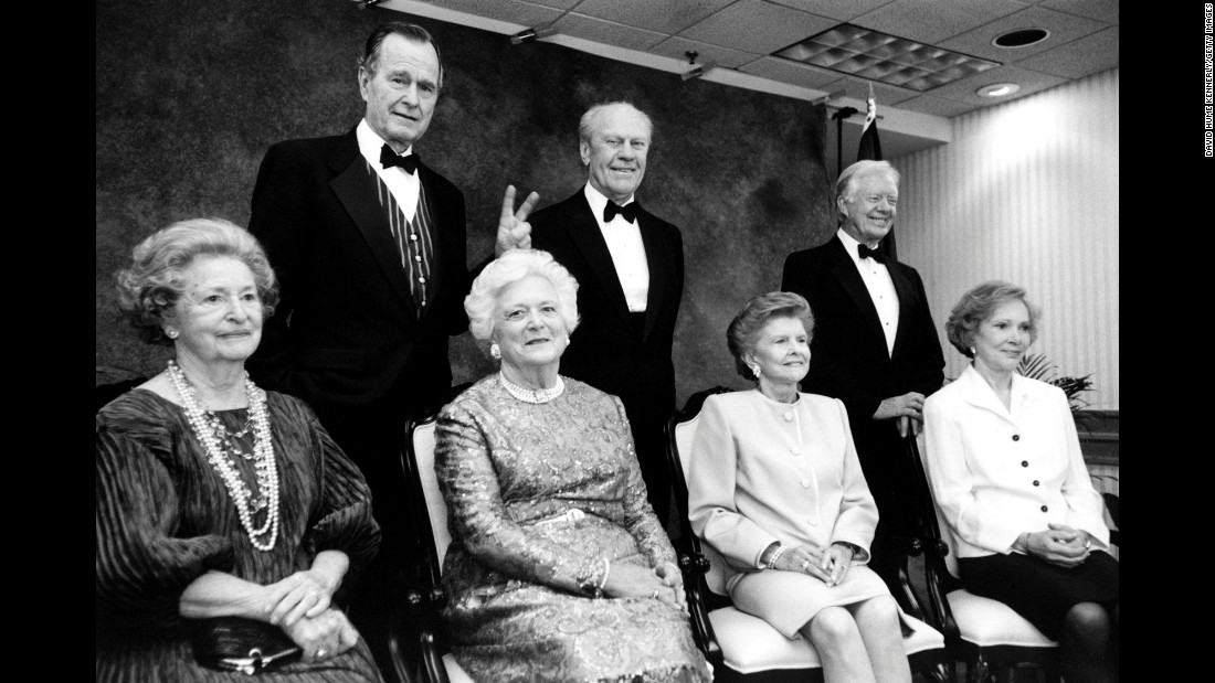 "President Bush gives his wife ""bunny ears"" during an event at the Gerald R. Ford Library on April 16, 1997. Also pictured are former Presidents Ford and Jimmy Carter, as well as former first ladies Lady Bird Johnson, Betty Ford and Rosalynn Carter."