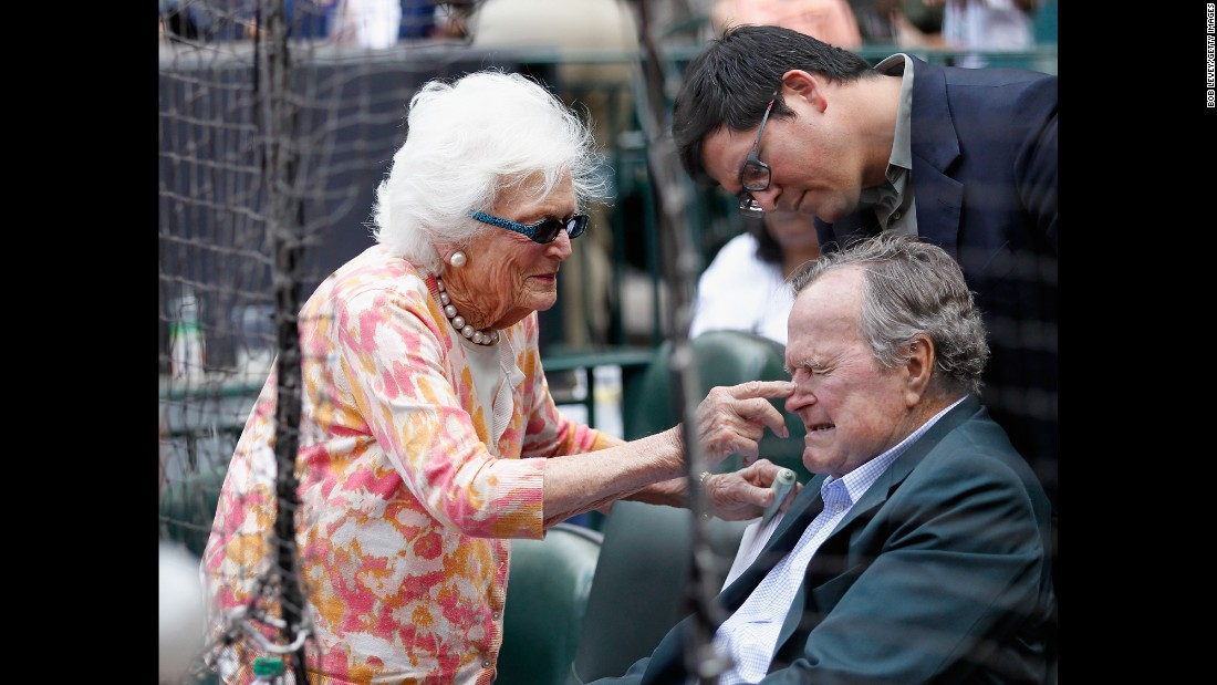 Barbara Bush puts some sunscreen on her husband's nose as they get ready to watch the Seattle Mariners play the Houston Astros in a Major League Baseball game on May 3, 2015.