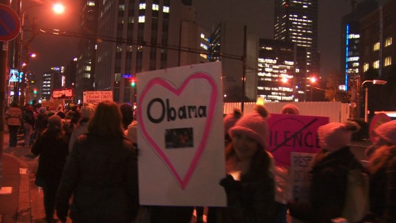 A woman holds a sign supporting Barack Obama during a Friday march in Tokyo organized by Democrats Abroad of Japan.