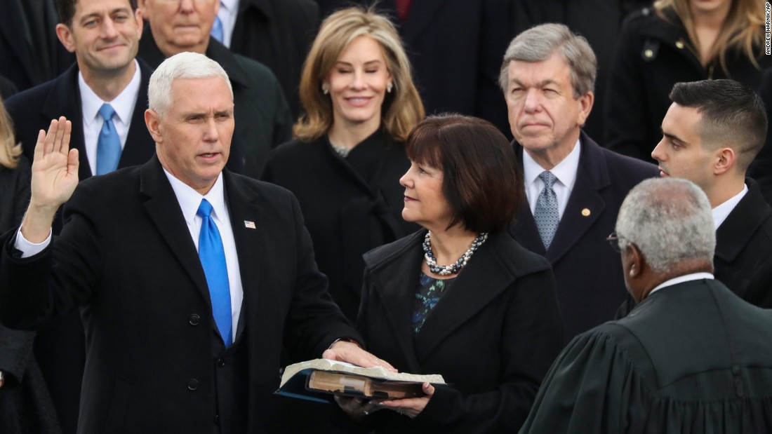 Vice President Mike Pence is sworn in by Justice Clarence Thomas as Pence's wife, Karen, holds the bible.