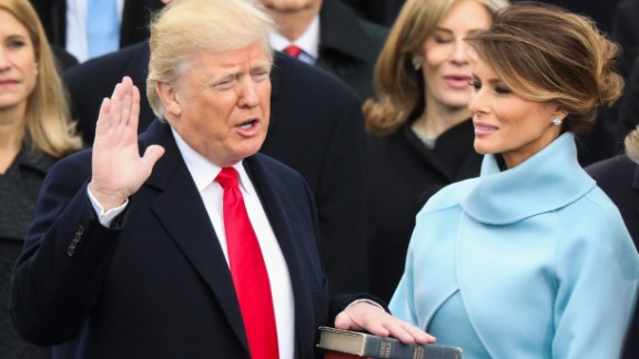 Trump is sworn in as President with his wife, Melania, at his side.