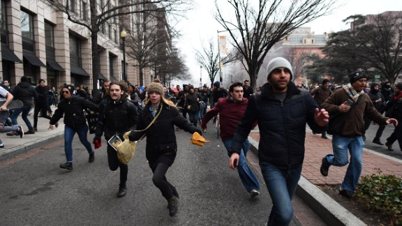 A pair of police officers were injured and at least 95 protesters arrested after they smashed windows, damaged cars and threw rocks at police. Here, people flee one  scene.