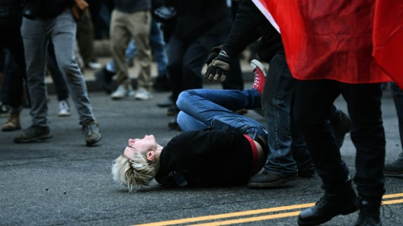 An anti-Trump protester reacts after being hit by a paintball fired by police.