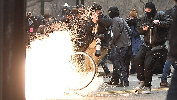 """A police flash-bang grenade explodes during a clash with protesters. """"Pepper spray and other control devices were used to control the criminal actors and protect persons and property,"""" police said."""