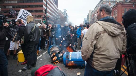 Protesters set trash cans ablaze.