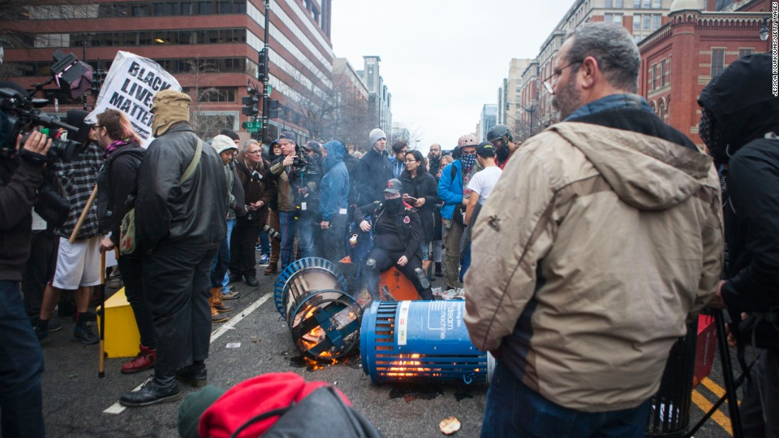 Protesters set trash cans ablaze.
