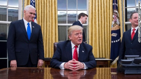 TOPSHOT - US President Donald Trump (C) speaks to the press as he waits at his desk before signing conformations for General James Mattis as US Secretary of Defense and General John Kelly as US Secretary of Homeland Security, as Vice President Mike Pence (L) and White House Chief of Staff Reince Priebus (R) look on, in the Oval Office of the White House  in Washington, DC, January 20, 2017. / AFP / JIM WATSON        (Photo credit should read JIM WATSON/AFP/Getty Images)