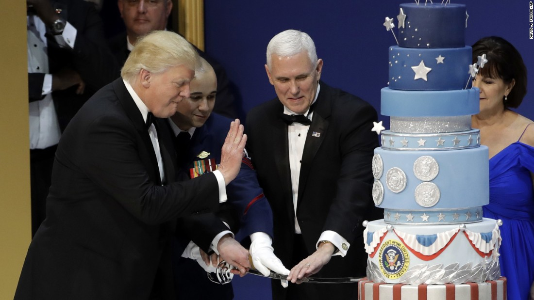 President Donald J. Trump, left, and Vice-President Mike Pence, right, are helped by Coast Guard Petty Officer 2nd Class Matthew Babot, center, as they cut a cake at The Salute To Our Armed Services Inaugural Ball.