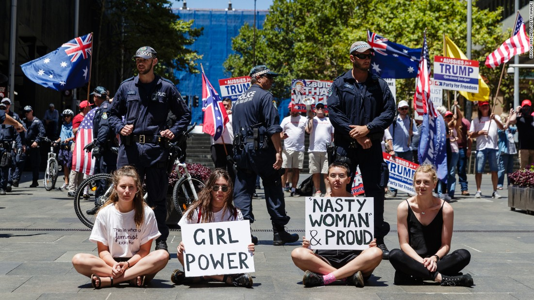 Protesters sit in front of police separating them from a small pro-Trump rally in Sydney.