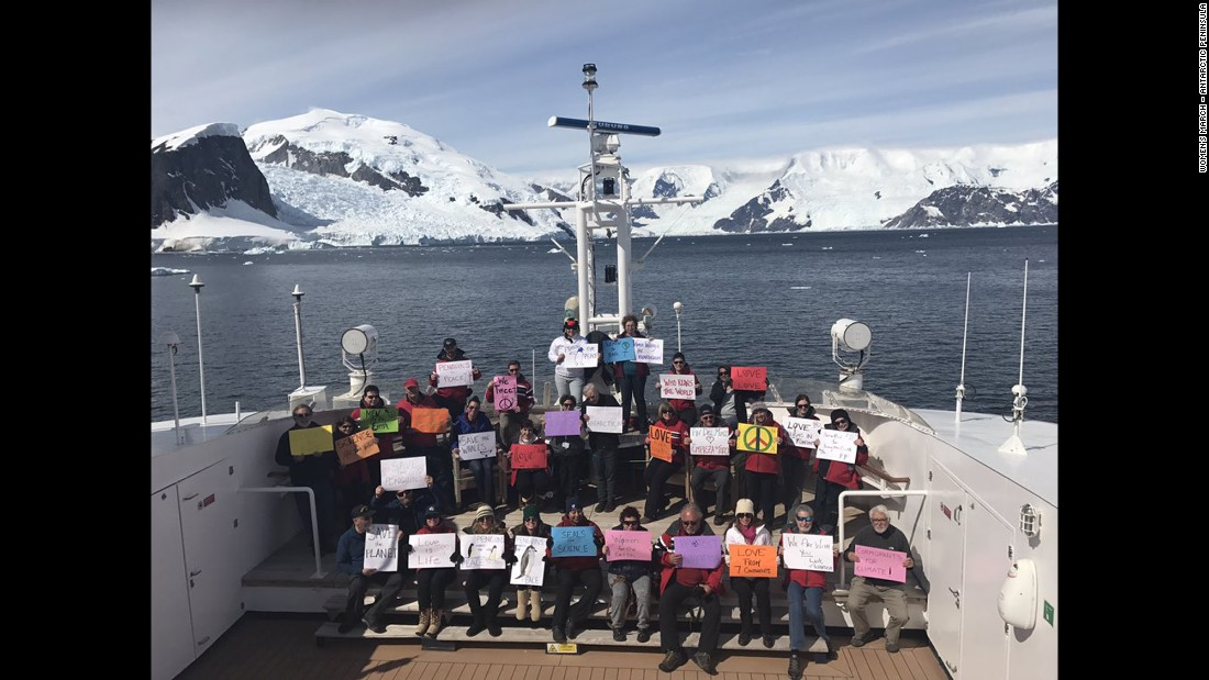 "Supporters in the Antarctic Peninsula take part in a women's march on Saturday, January 21. According to organizers, the march includes about 30 people who are eco-minded tourists and non-government scientists. Some held signs saying,  ""Penguins for Peace"" and ""Seals for Science."""