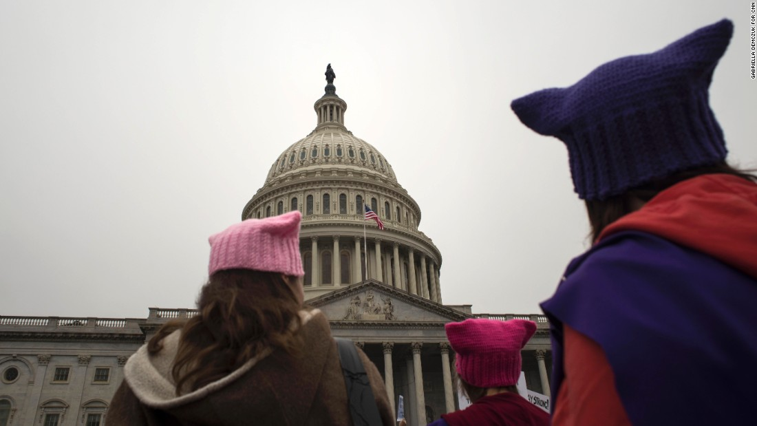 Women with cat hats walk past the Capitol.