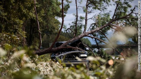 SAVANNAH, GA - OCTOBER 8: An abandoned car damaged by a fallen tree sits along Interstate 16, October 8, 2016 in Savannah, Georgia. Across the Southeast, Over 1.4 million people have lost power due to Hurricane Matthew which has been downgraded to a category 1 hurricane on Saturday morning. (Photo by Drew Angerer/Getty Images)