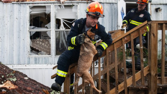 A firefighter carries a dog that was trapped inside a mobile home in Albany, Georgia, on Monday, January 23. Fire and rescue crews have been searching through the debris after severe storms hit southern Georgia over the weekend.