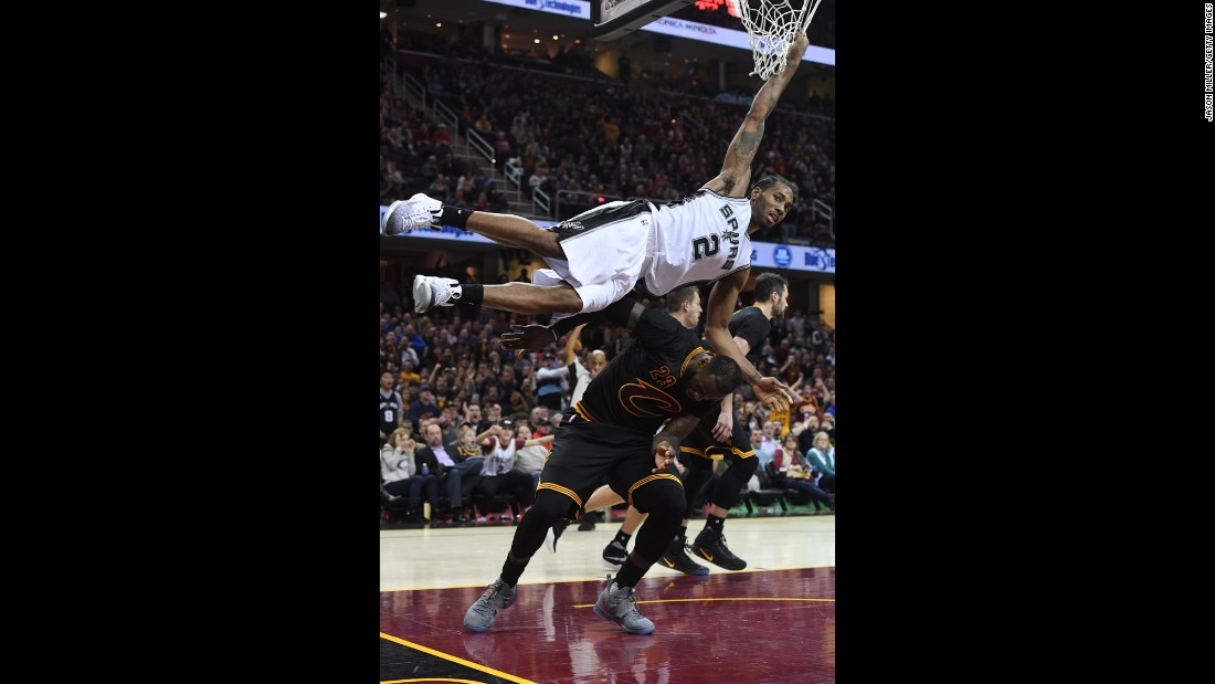 San Antonio's Kawhi Leonard hangs onto the net to avoid landing on Cleveland's LeBron James during an NBA basketball game in Cleveland on Saturday, January 21. Leonard had a career-high 41 points as San Antonio won in overtime 118-115.
