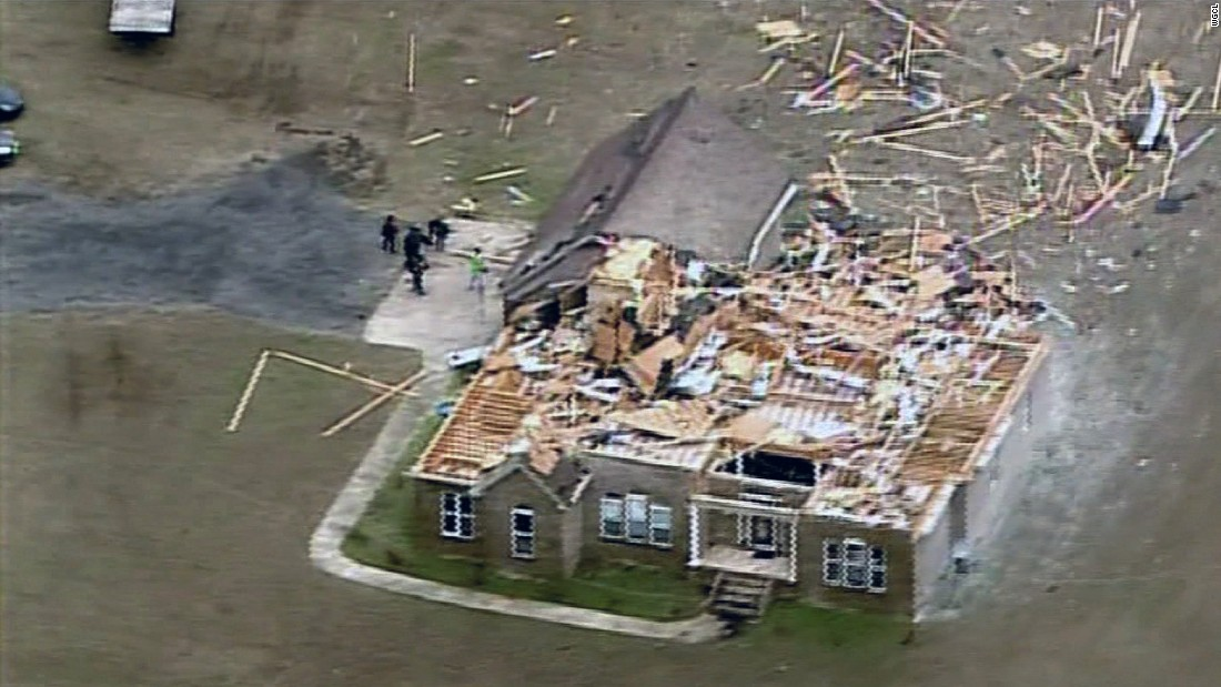 The tornado ripped through this home's roof and top level, strewing debris across the area.