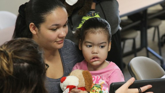 Melyssa Braga watches a video with her mother, Caroline, and a nurse.