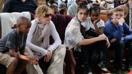 Madonna sits with her children (L to R) David Banda, Lourdes, Mercy James, and Rocco at Mkoko Primary School, one of the schools Madonna's Raising Malawi organization on April 2, 2013.