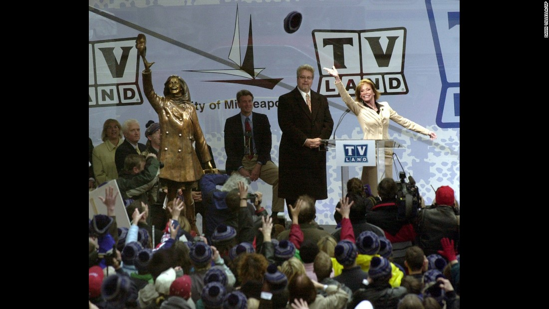 "Moore re-enacts her famous hat toss afer a bronze statue of her was unveiled in 2002. The statue was unveiled in Minneapolis, where ""The Mary Tyler Moore Show"" takes place."