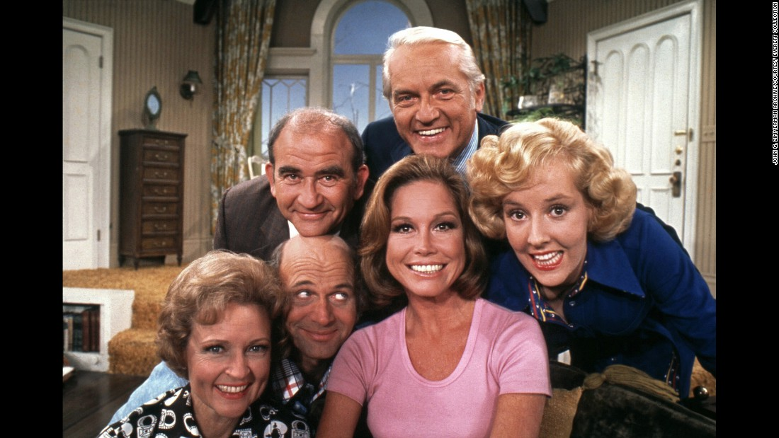"Moore, in the pink shirt, poses with cast members of ""The Mary Tyler Moore Show"" in 1974. Clockwise from Moore are Gavin MacLeod, Betty White, Ed Asner, Ted Knight and Georgia Engel. The show ended in 1977 but spurred several spinoffs, including ""Rhoda"" and ""The Lou Grant Show."""