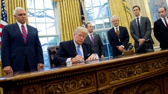 TOPSHOT - US President Donald Trump signs an executive order in the Oval Office of the White House in Washington, DC, January 23, 2017. Trump on Monday signed three orders on withdrawing the US from the Trans-Pacific Partnership trade deal, freezing the hiring of federal workers and hitting foreign NGOs that help with abortion. / AFP / SAUL LOEB        (Photo credit should read SAUL LOEB/AFP/Getty Images)