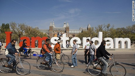 "TO GO WITH AFP STORY by Gerald de Hemptinne (FILES) People ride their bicycle by a giant logo ""I Amsterdam"" on the Museum Square in Amsterdam, 22 April 2007. The Dutch government has taken a trend to promote eco-friendly cities a step further than its European neighbors by announcing firm measures to discourage cars and driving. AFP PHOTO / ANP PHOTO / RUUD TAAL (Photo credit should read Ruud Taal/AFP/Getty Images)"