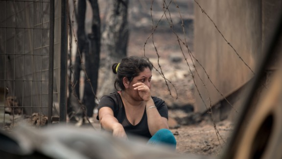 A woman wipes tears amid the remains of Santa Olga, a small town ravaged by the fires.
