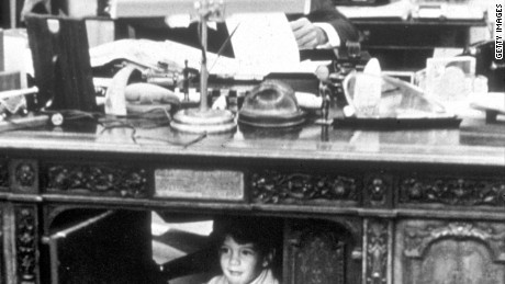 John F. Kennedy works at the Resolute Desk in the Oval Office while his son, John Jr., peeks out from the panel underneath the desk.