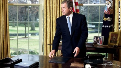 President George W. Bush gets up from his desk in the Oval Office of the White House after finishing a call to former First Lady Nancy Reagan on the occasion of former US President Ronald Reagan's 90th birthday 15 February, 2001 in Washington, DC..