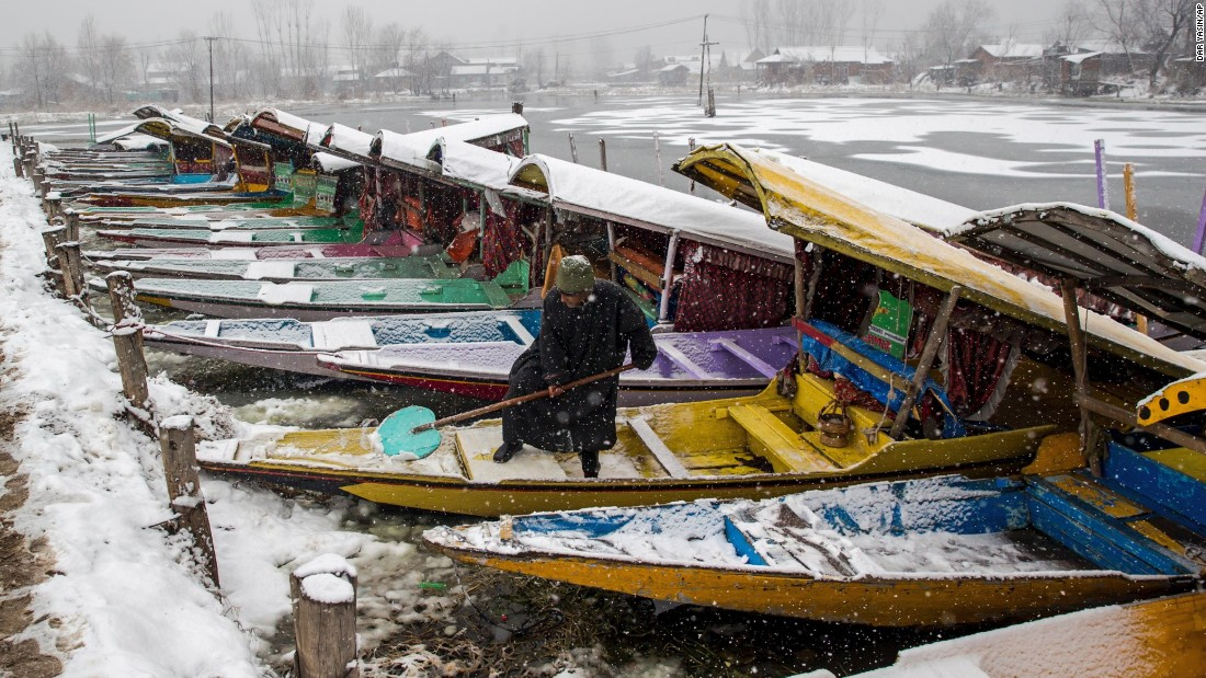 A man clears snow from his boat in Srinagar, India, on Tuesday, January 17.
