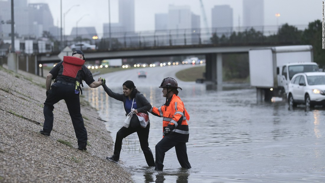 A woman is helped out of a flooded road in Houston on Wednesday, January 18.