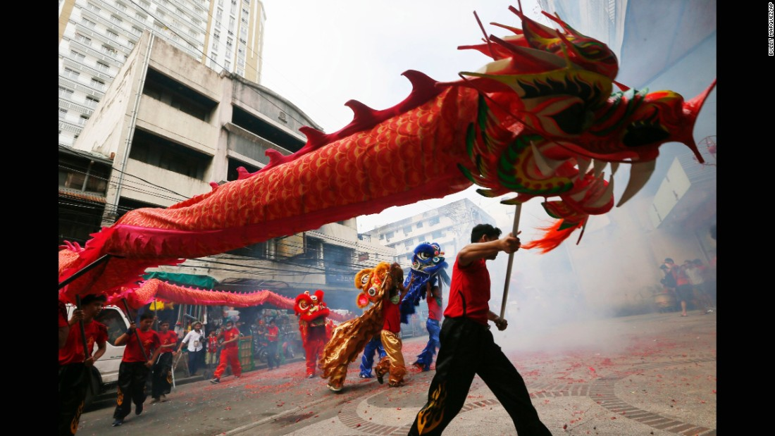 A dragon dances with lions in Manila, Philippines.