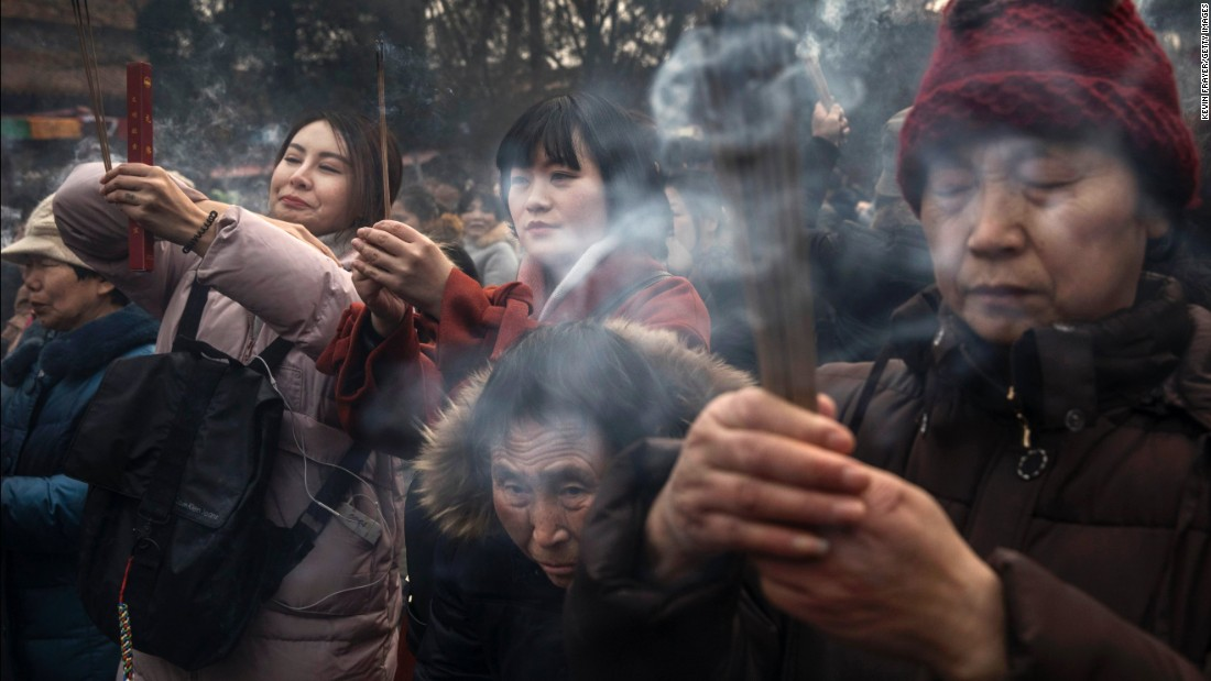 Worshippers pray for good luck and fortune on the first day of the Lunar New Year at the  Yonghe Temple in Beijing.