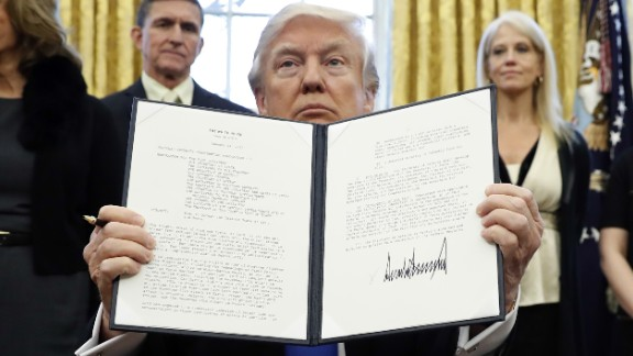 """President Donald Trump holds up a signed executive memorandum calling on the Pentagon to """"develop a comprehensive plan to defeat ISIS."""""""