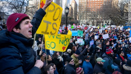 Ben Odom, left, of New York, and others gather in New York's Battery Park Sunday, Jan. 29, 2017, protesting President Donald Trump's immigration order. The order has sowed chaos and outrage across the country Sunday, with travelers detained at airports, panicked families searching for relatives and protesters registering opposition to the sweeping measure that was blocked by several federal courts.(AP Photo/Craig Ruttle)