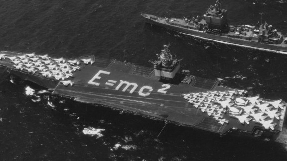 Aerial view of the world's first nuclear-powered aircraft carrier the USS Enterprise (CVN-65) of the United States Navy, with physicist Albert Einstein's E = mc 2 mass--energy equivalence equation laid out on the flight deck, is escorted by the missile cruiser USS Long Beach (centre) and the missile frigate, USS Bainbridge, during Operation Sea Orbit, the first circumnavigation of the world by nuclear-powered surface warships,31 July 1964 off Bahia de Pollença, Mallorca, Spain.  (Photo by Keystone/Getty Images)