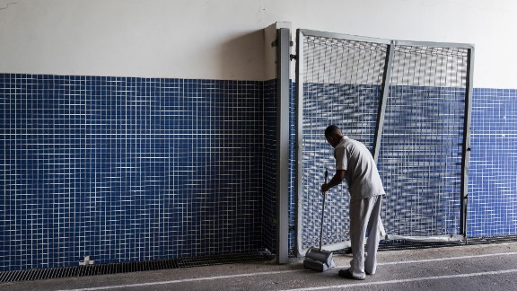 A man cleans one of the entrances to the stadium.