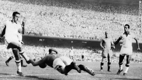 Swedish goalkeeper Kalle Svensson dives to block the ball in front of Brazilian forward Ademir 09 July 1950 during their World Cup final pool match.