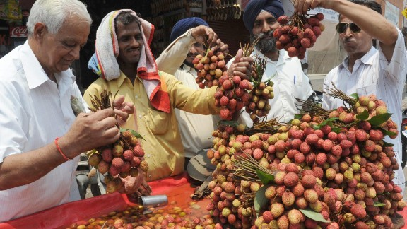 Indian fruit vendor Hari Ram (2L) offers lychees to customers from his roadside stall in Amritsar on June 1, 2009. Temperatures in northern India are currently hovering around 46 degrees Celsius with lychees are known to be a cooling fruit in the heat and are in heavy demand in the summer season.    AFP PHOTO/NARINDER NANU (Photo credit should read NARINDER NANU/AFP/Getty Images)