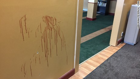 A wall at the Quebec Islamic Cultural Center, where six people were killed Sunday, is stained with blood and dotted with bullet holes.